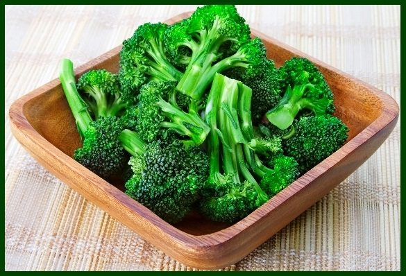 A wooden bowl of fresh, steamed broccoli.